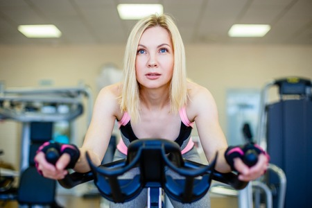 Happy blonde doing indoor biking in a fitness club 版權商用圖片