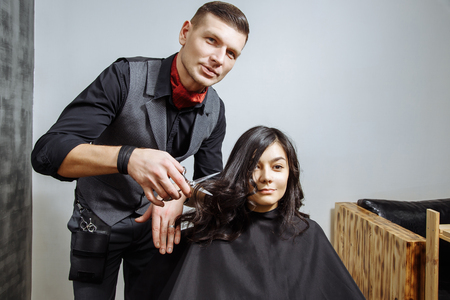 Professional male hairdresser cutting hair to a female client at design salon 免版税图像