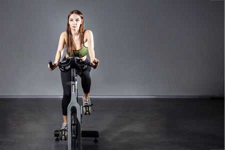Young woman working out on the exercise bike at the gym 写真素材