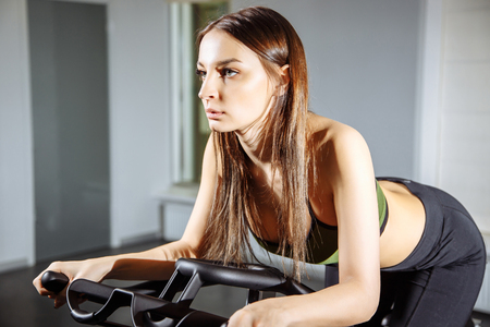 Young woman working out on the exercise bike at the gym, intense cardio workout