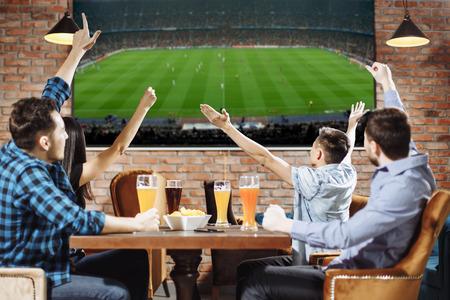 Sieg! Gruppe junge schöne Freunde, die fernsehen und für ihr Team beim Stillstehen in der Kneipe zujubeln. Standard-Bild