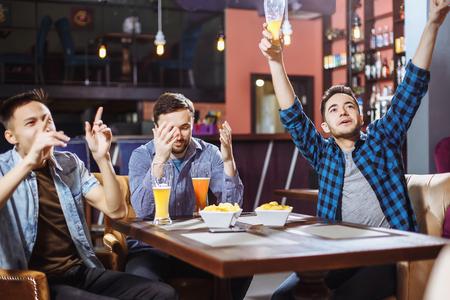 Nette Freunde , die Spaß ein Fußballspiel auf Fernsehen und Bier Fassbier am Barzähler in der Kneipe essen Standard-Bild