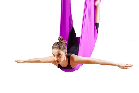 Young beautiful yogi woman doing aerial yoga practice in purple hammock.