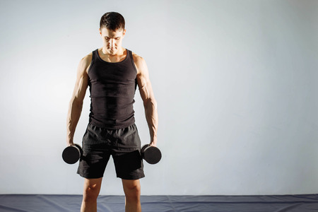 Muscular young man doing heavy weight exercise for biceps. Stock Photo