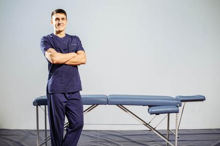 Portrait de jeune homme souriant en uniforme près de canapés de massage