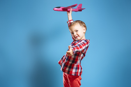 Little cute girl with a toy plane showing her thumb up Banco de Imagens