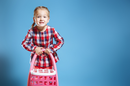 Little cute girl with toy suitcase on blue background Stock Photo