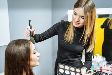 Makeup artist creating beautiful makeup for brunette model . Beauty concept