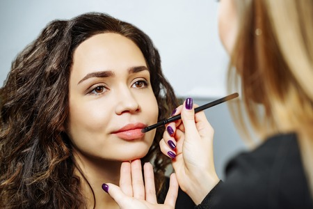Beautiful model girl applying lipgloss. Lipstick. Professional Make-up