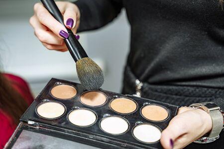 Female makeup artist with cosmetics at work close-up. 版權商用圖片 - 127781196