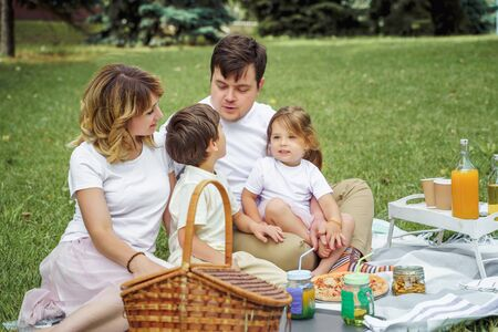 Happy family with kids resting on the grass during a picnic. Happiness and harmony in family life
