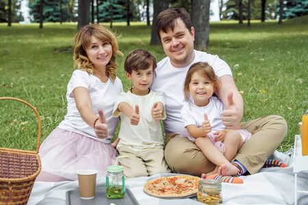 Portrait of happy family showing thumbs up at picnic. 版權商用圖片