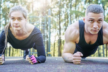 Portrait of young sporty couple doing the plank exercise outdoors 版權商用圖片