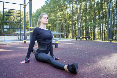 Athletic fit woman doing splits exercises outdoors.