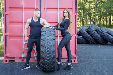 Attractive athletic couple posing near the tire after a workout. 版權商用圖片