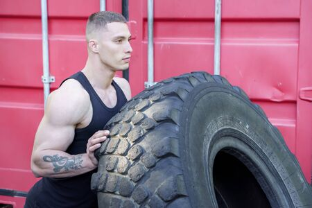 Strong young man flipping tyre while exercising outdoor. CrossFit