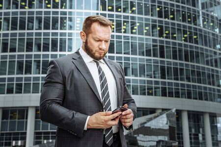Business man wearing suit and using smartphone near office