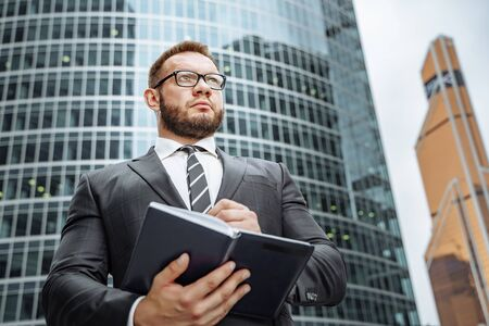 Portrait of a successful business man in a suit and glasses with a notebook in his hands