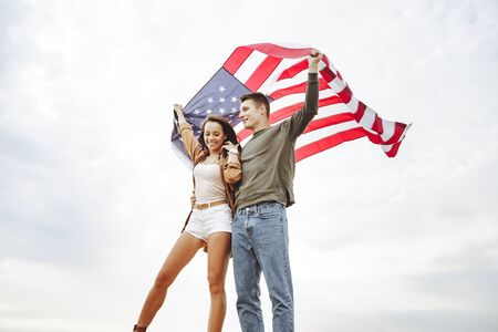 Happy couple holding the American flag in nature. Independence Day, lifestyle, travel concept. 版權商用圖片