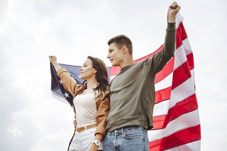 Portrait of a happy couple with an American flag against a blue sky. Independence Day, lifestyle, travel concept