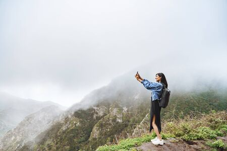 Happy woman tourist taking selfie using smartphone on top of a mountain.