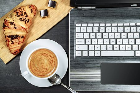 Coffee, croissant and laptop on the table. Breakfast