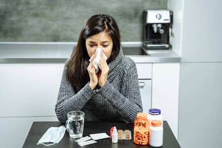 Sick woman with medicine blowing nose to paper wipe at home. 版權商用圖片