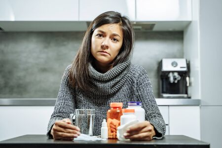 Portrait of a sad woman holding many pills and a handkerchief in her hands in the kitchen.