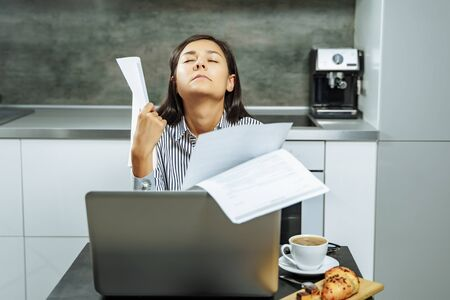 Tired young woman with closed eyes holding paper in hands in the kitchen