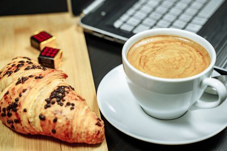 Coffee, croissant and laptop on the table. Business breakfast concept Banco de Imagens
