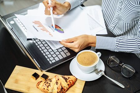 Coffee, croissant and female hands holding documents on the desktop. Business breakfast concept.