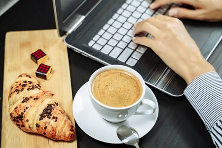 Croissant with chocolate and coffee on the desktop. Business breakfast concept