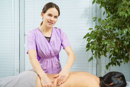 Portrait of a smiling massage therapist woman massaging a young brunette in a medical center Banco de Imagens