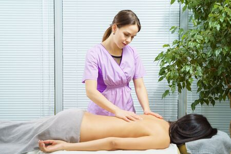 Young woman receiving back massage from female physiotherapist.