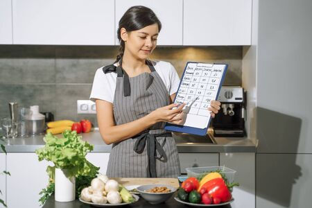 Young woman nutritionist holding a comparative table of calorie products in the hands in the kitchen. Banco de Imagens