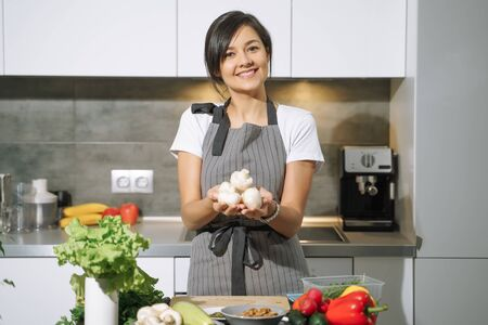 Young smiling woman holding mushrooms in her hands in the kitchen. Proper nutrition and health concept