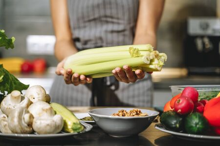 Close up of female hands holding fresh celery in the kitchen. Proper nutrition and health concept.