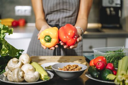 Close up of female hands holding fresh yellow and red peppers in their hands in the kitchen