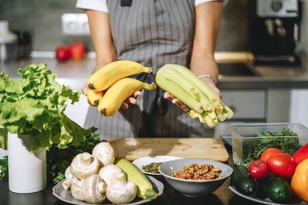 Close up of female hands holding fresh celery and bananas in the kitchen. Proper nutrition and health concept