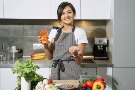 Young attractive woman showing nutritional supplements or vitamins in the kitchen