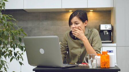 Frightened young woman reading the news on the Internet and drinking pills or vitamins in the kitchen at home.