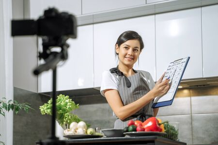 Young smiling woman nutritionist showing a comparative table of calorie foods and recording video on a camera in the kitchen