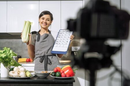 Young smiling woman in an apron holding celery and a comparative table of calorie content of products in her hands and recording video on a camera in the kitchen.