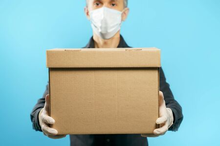 Close-up of a cardboard box in the hands of a young man in a medical protective mask and gloves on a blue