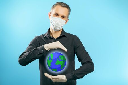 Portrait of a young man in a protective medical mask and gloves holding a globe in his hands on a blue