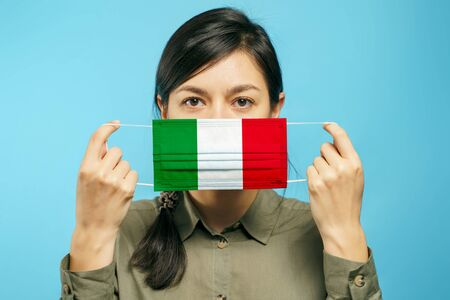 Young beautiful woman holding a medical protective mask in their hands with the Italian national flag on a blue