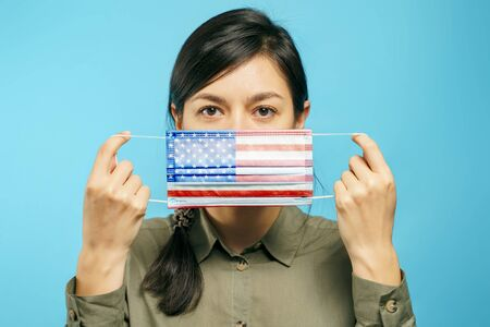 Young beautiful woman holding a medical protective mask in their hands with the American national flag on a blue Banco de Imagens