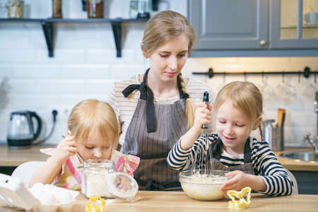 Happy family young mother and two little daughters preparing dough for pancakes or cookies together in the kitchen.