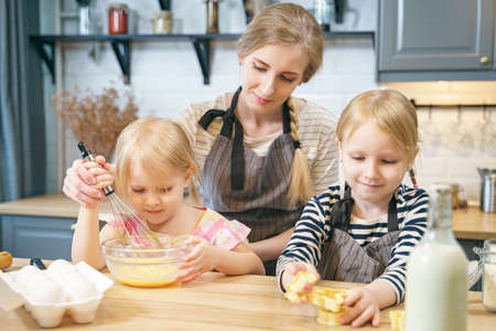 Happy family young mother and two little daughters making dough for pancakes or cookies together in the kitchen. Standard-Bild