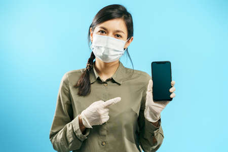 Portrait of a young woman in a protective medical mask and gloves pointing to the screen of a smartphone on a blue background. Copy space.